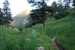 Rastro por un sendero a partir de una montaña que pasa por alto otra en la puesta del sol T imágenes de archivo libres de regalías