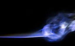 Rastros azules sedosos del humo en negro Imagenes de archivo
