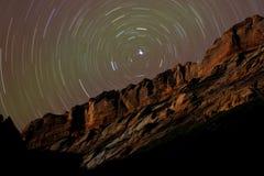 Rastros de la estrella alrededor de la estrella polar sobre los acantilados del desierto Fotografía de archivo