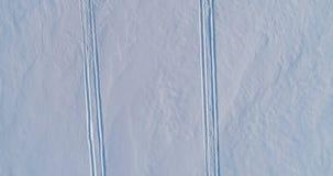 Rastros de la moto de nieve en nieve Vídeo aéreo almacen de metraje de vídeo
