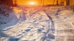Rastros de las ruedas de coche en un camino nevoso Imagen de archivo libre de regalías