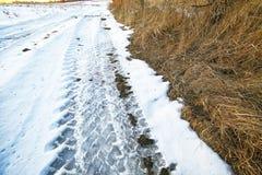 Rastros de las ruedas de coche en un camino nevoso Fotos de archivo