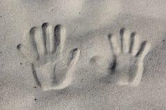 Rastros de manos en la arena Foto de archivo