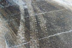 Rastros de ruedas de coches en el camino con fango y la nieve blanca Fondo del invierno Foto de archivo