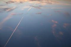 Rastros del avión en una puesta del sol al revés fotos de archivo