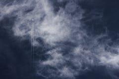 Rastros del avión y del vapor de reacción que van derecho para arriba a través de un cielo azul profundo nublado Imagenes de archivo