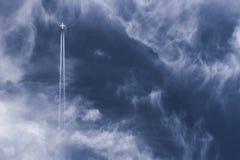 Rastros del avión y del vapor de reacción que van derecho para arriba a través de un cielo azul profundo nublado Foto de archivo