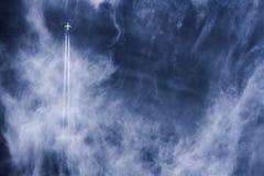 Rastros del avión y del vapor de reacción que van derecho para arriba a través de un cielo azul profundo nublado Fotografía de archivo