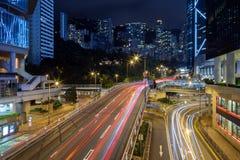 Rastros y edificios de la luz en Hong Kong en la oscuridad Fotografía de archivo libre de regalías