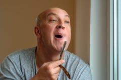 Rasuren eines Mannes mit einem geraden Rasiermesser stockbild