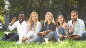 Rasy grupa ucznie siedzi wpólnie na zielonym gazonie kampus zbiory