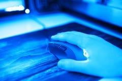 Ratón azul del ordenador con la mano humana en el contexto del bokeh del mousepad Fotos de archivo