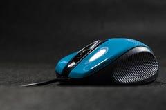 Ratón del ordenador del color azul brillante Detalles negros plástico Tecnologías modernas Fondo negro Ordenador fotos de archivo