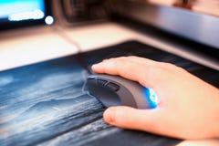 Ratón del ordenador con la mano humana en el contexto del bokeh del mousepad Foto de archivo libre de regalías