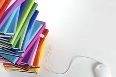 Ratón del ordenador tapado en la pila de arco iris-color Imagenes de archivo