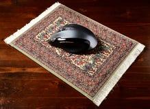 Ratón en un cojín de alfombra real Fotos de archivo