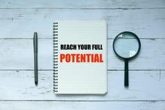 Rat und Motivation Draufsicht des Stiftes, der Lupe und des Notizbuches geschrieben mit Reichweite Ihr volles Potenzial auf weiße lizenzfreie stockbilder