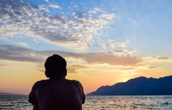 Rata Beach, Brela, Croatia. The guy on the background of beautiful sunset over the sea. Punta Rata Beach, Brela, Croatia royalty free stock photo