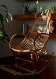 Ratan rocking chair in a bohemian home with vintage decor. And beautiful sunlight royalty free stock photo