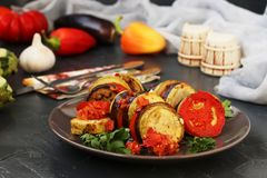 Ratatouille is located on a plate on a dark background. Baked vegetables: aubergines, zucchini and tomatoes royalty free stock image