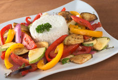 Ratatouille with Rice. Ratatouille of zucchini, eggplant, tomato, bell pepper and onion with cooked rice and parsley on top (Selective Focus, Focus on the front royalty free stock images