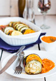 Ratatouille sauce served in a round plate, fork, knife on a whit Royalty Free Stock Images