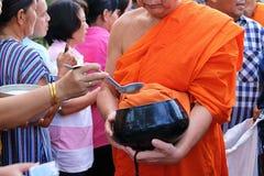 Ratchaburi,泰国- 2017年4月14日:佛教给的施舍用对一个和尚的食物在Songkran天早晨 图库摄影