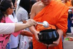 Ratchaburi,泰国- 2017年4月14日:泰国人投入食物给一个和尚`施舍在Songkran节日天滚保龄球的s 库存图片