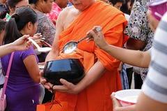 Ratchaburi,泰国- 2017年4月14日:泰国人投入食物给一个和尚`施舍在Songkran节日天滚保龄球的s 免版税库存图片