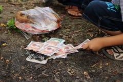 Ratchaburi, Tailandia - 4 de abril de 2017: Quema del dinero falso hecha de los materiales de papel durante el festival ming o la Imagen de archivo
