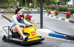 RATCHABURI, TAILANDIA - 29 DE DICIEMBRE: Una madre del asiático compite con un carro fotografía de archivo libre de regalías