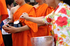 Ratchaburi, Thailand - April 14, 2017 : Hands of people while put food to a Buddhist monk`s alms bowl  in Songkran festival Day. Ratchaburi, Thailand - April 14 Royalty Free Stock Photography