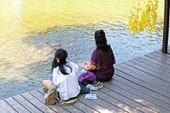 Ratchaburi/Thailand - April 21 2018: Thaise mensen die vissen voeden bij de rivier in openbaar park stock foto's