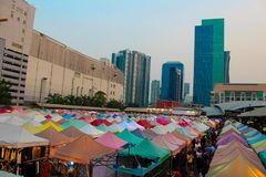 Ratchada Rot Fai Market at Midday. Ratchada Rot Fai Market during the daytime/evening. The colorful tents contrast with the tall green, black, and white Stock Image