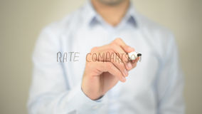 Rate Comparison , man writing on transparent screen Royalty Free Stock Photo