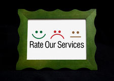 Rate Our Services con feliz iconos tristes en la pizarra Foto de archivo