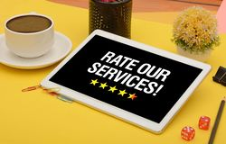 Rate our Services Stars with coffee cup and tablet royalty free stock photo