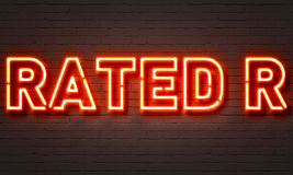 Rated R neon sign. On brick wall background Royalty Free Stock Image