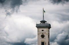 Rathaus-Glockenturm von Lemberg mit ukrainischer Flagge an der Spitze gegen den stürmischen bewölkten Himmel, Ukraine Lizenzfreie Stockfotografie