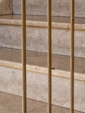 Rather grungy steps through or behind bars. Royalty Free Stock Photography