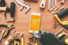Rating customer service for handyman repair and maintenance task. Repairman using mobile phone, top view stock photography