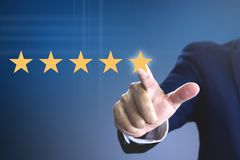Rating with five stars for a satisfaction and enjoyment. Hand of a man giving high score with five golden stars rating for movie or television programme or royalty free stock images