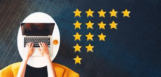 Rating Theme with person using a laptop. On a white table royalty free stock image