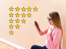 Rating Theme with woman using a tablet stock photos