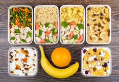 Ration of balanced food in plastic containers on dark table. Daily ration of balanced food in plastic containers on dark table. Top view Stock Image