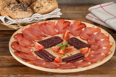 Ration cured pork loin and sausage decorated with cherry tomatoes Royalty Free Stock Image