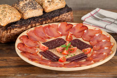 Ration cured pork loin and sausage decorated with cherry tomatoes Royalty Free Stock Photo