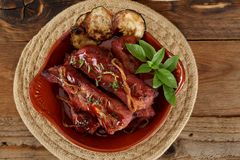 Ration of pork ribs with barbecue sauce decorated with zucchini chips and basil. Horizontal shot Royalty Free Stock Photo