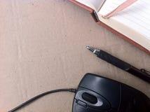 Ratón y cuaderno del ordenador con la pluma Imagen de archivo