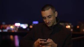 Rato sonriente del hombre que toma el selfie o la foto de la visión al aire libre en la luz de la noche Sirva el SMS que manda un almacen de video